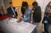 Dan Hartman (left) shows Chicago students how to assemble parts via video projection equipment