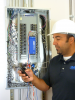 A DENT Instruments, Inc. facilities engineer uses the ELITEpro XC Power Meter to monitor consumption at an electrical panel